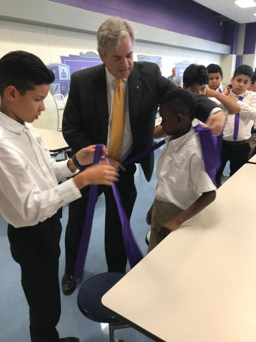 Mayor Adler helps sixth-grade students learn to tie their ties for the first time